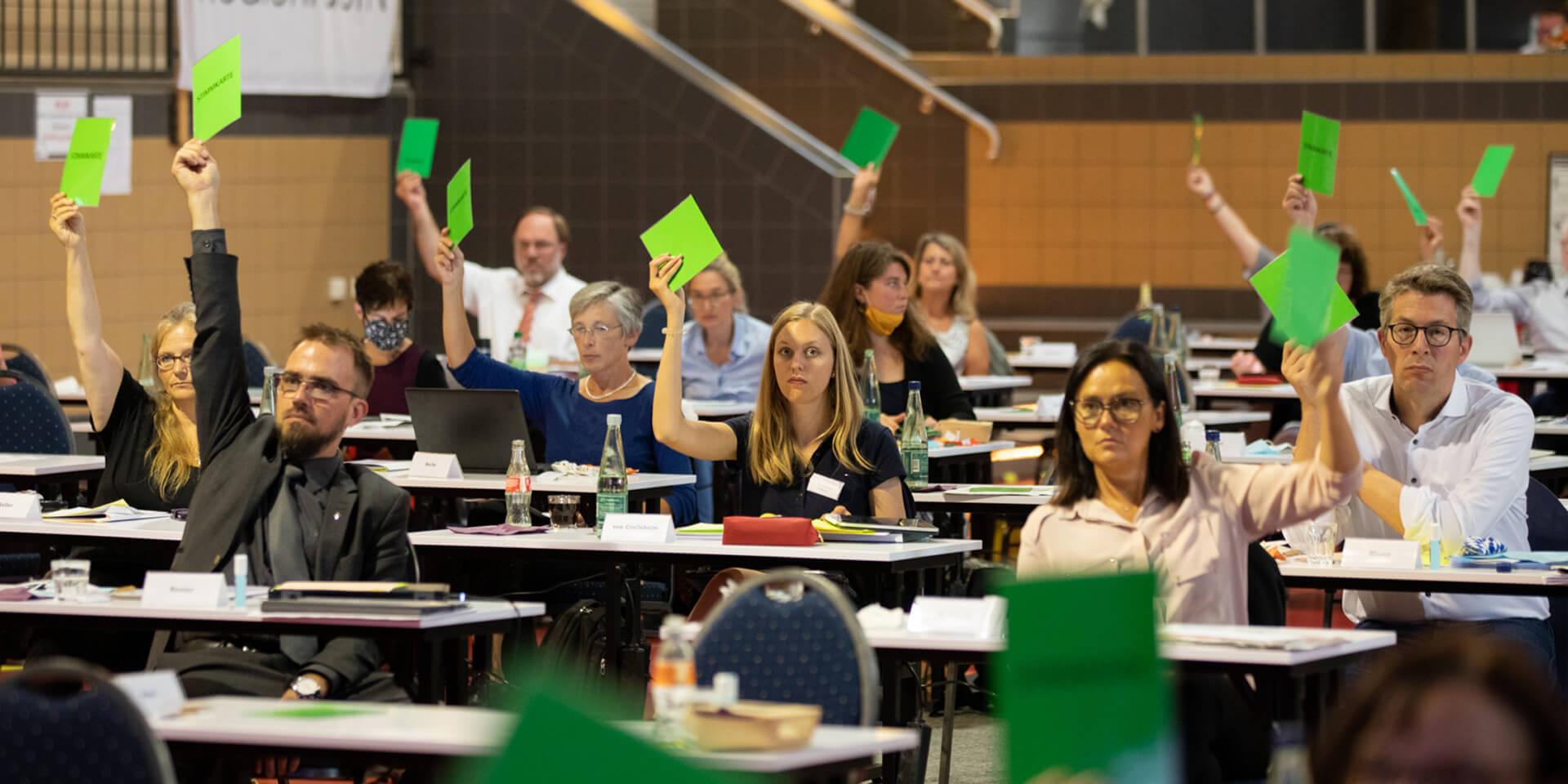 Landessynodale stimmen mit grüner Stimmkarte ab