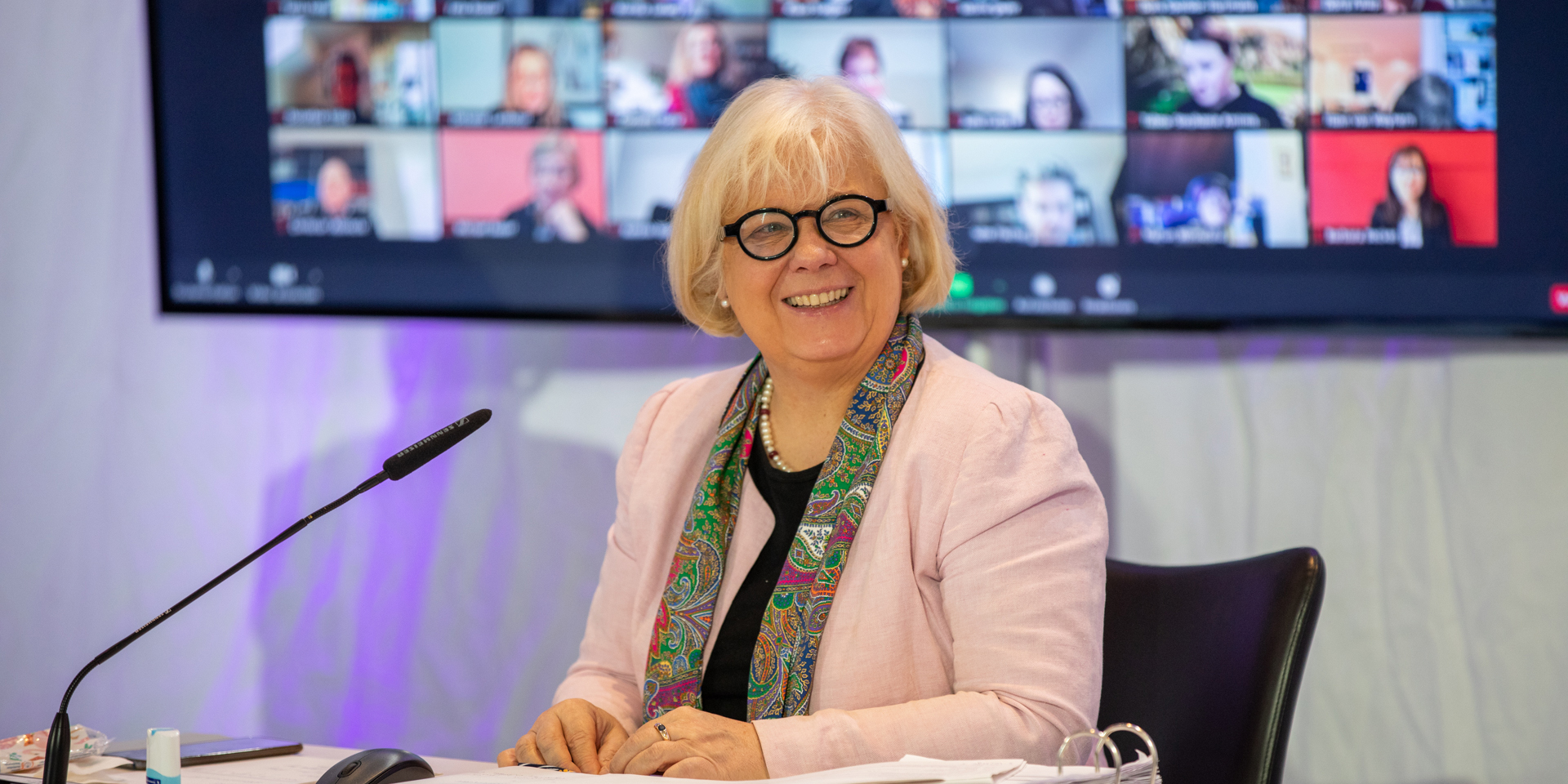 Synodalpräsidentin Annekathrin Preidel vor einem Bildschirm mit den Landessynodalen auf Zoom.
