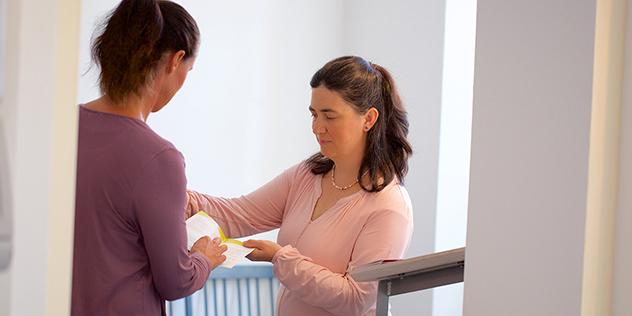 Eine Frau erläutert einer anderen einen Flyer.,© ELKB/unit4