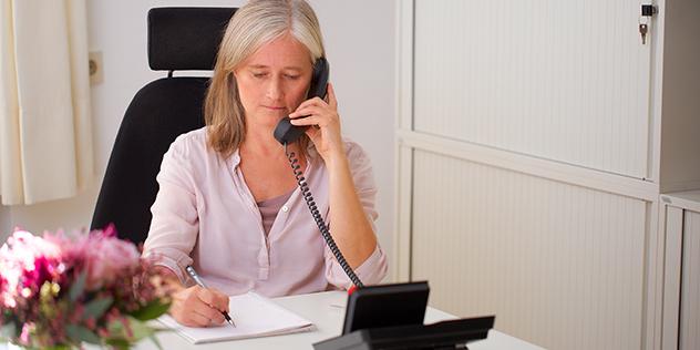 Eine Mitarbeiterin der Fachstelle berät am Telefon,© ELKB/unit4